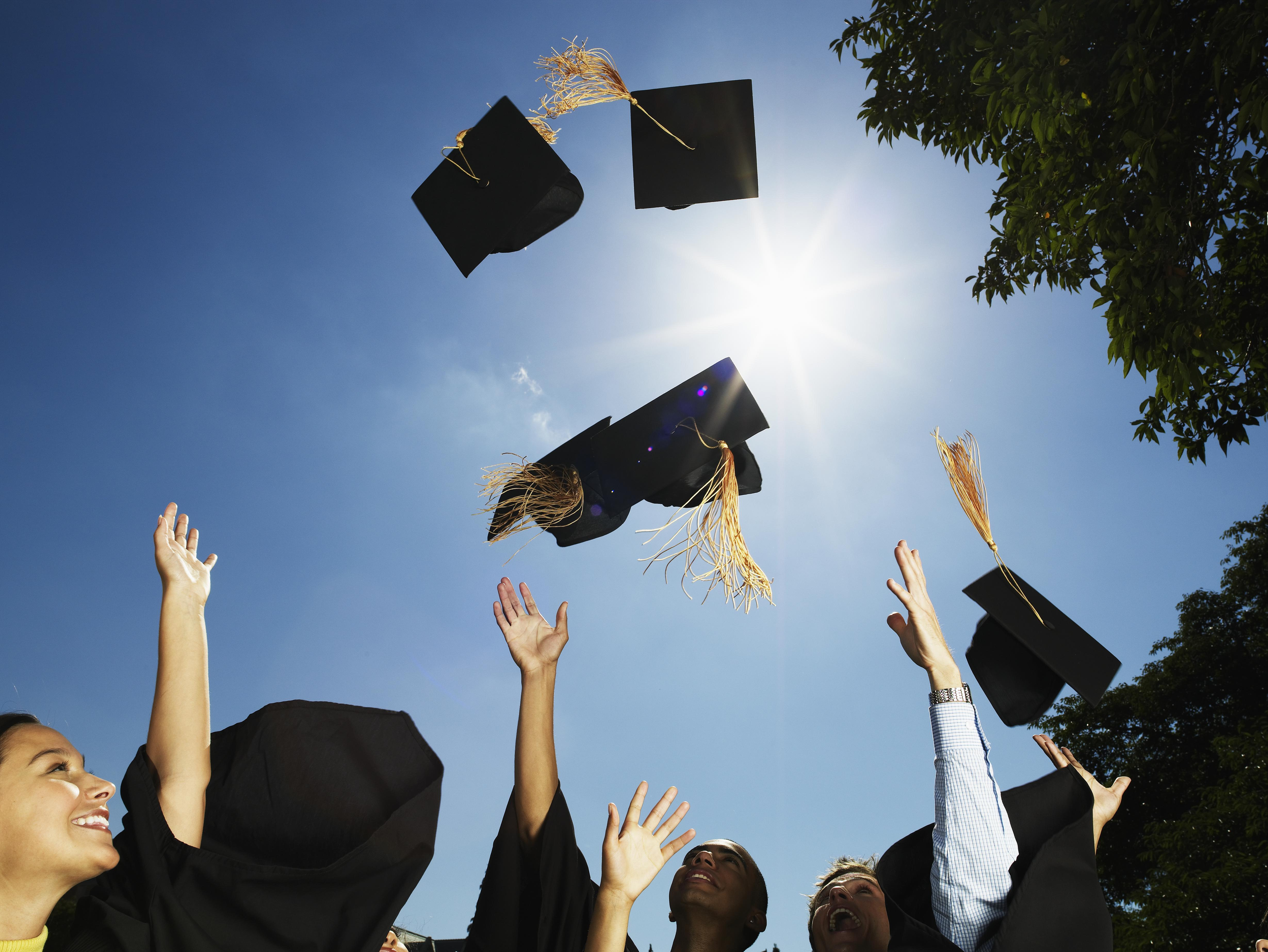 Group of graduates throwing mortar boards in air