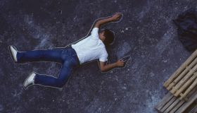 Man with gun lying on ground, chalk outline around him, elevated view