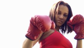 Young woman wearing boxing gloves, portrait, low angle view