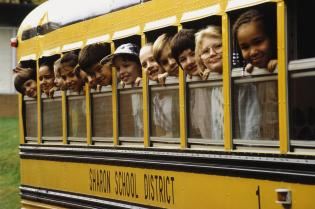 School children looking out school bus windows.