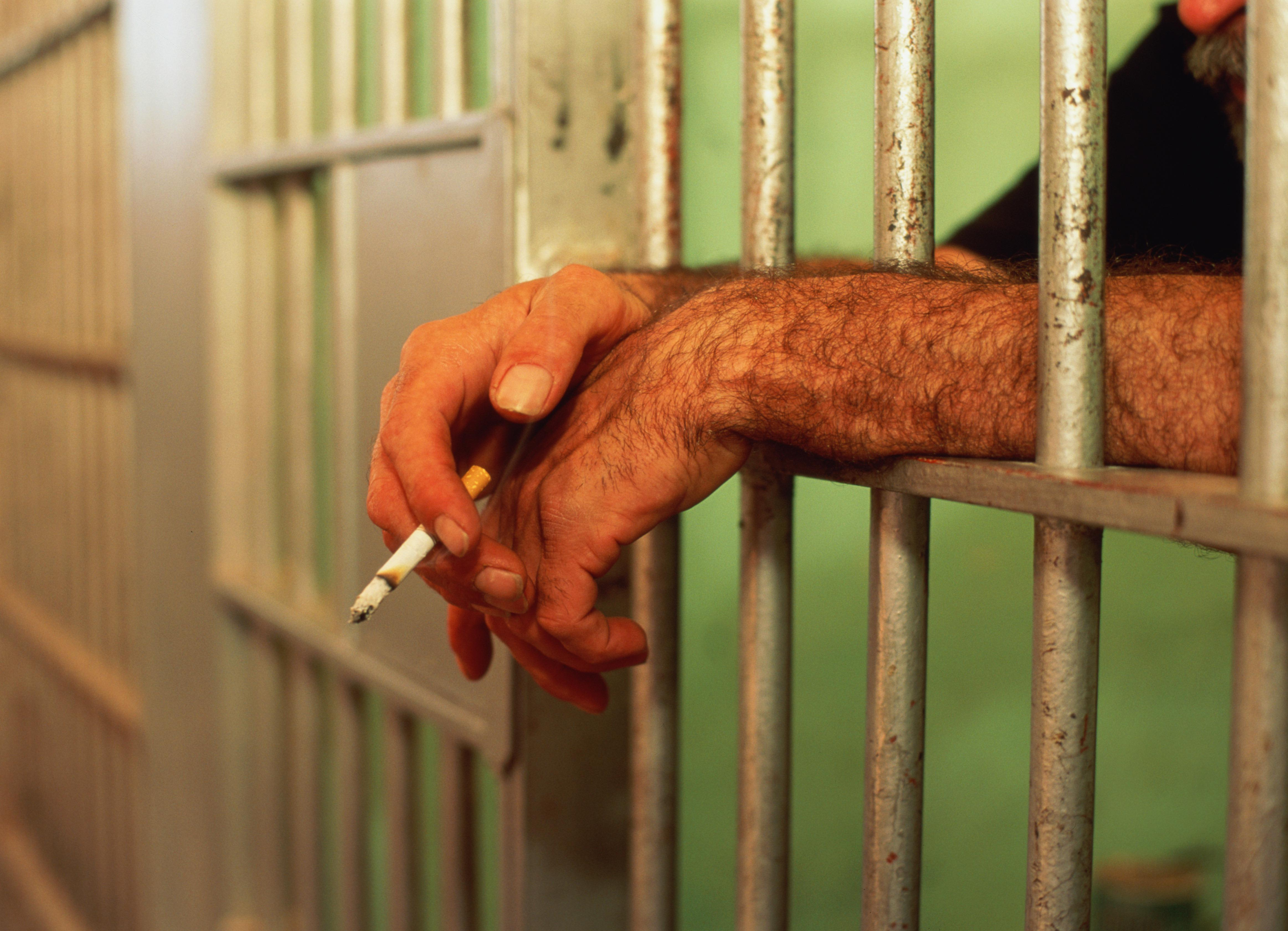 Man's hands poking through bars of jail cell, holding lit cigarette