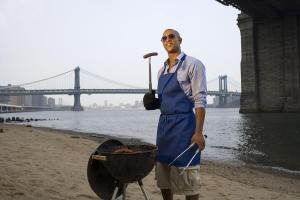 Young man cooking barbecue on beach, smiling