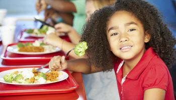 Elementary Pupils Enjoying Healthy Lunch In Cafeteria