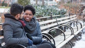 Loving Multi-Ethnic Couple sitting on a park bench
