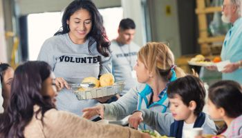 Volunteer serving healthy meal to families in food bank