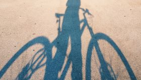 Shadow Of Man With Bicycle On Road During Sunny Day