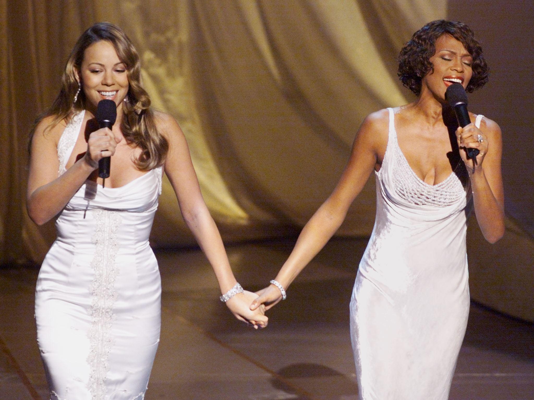 Singers Mariah Carey (L) and Whitney Hou