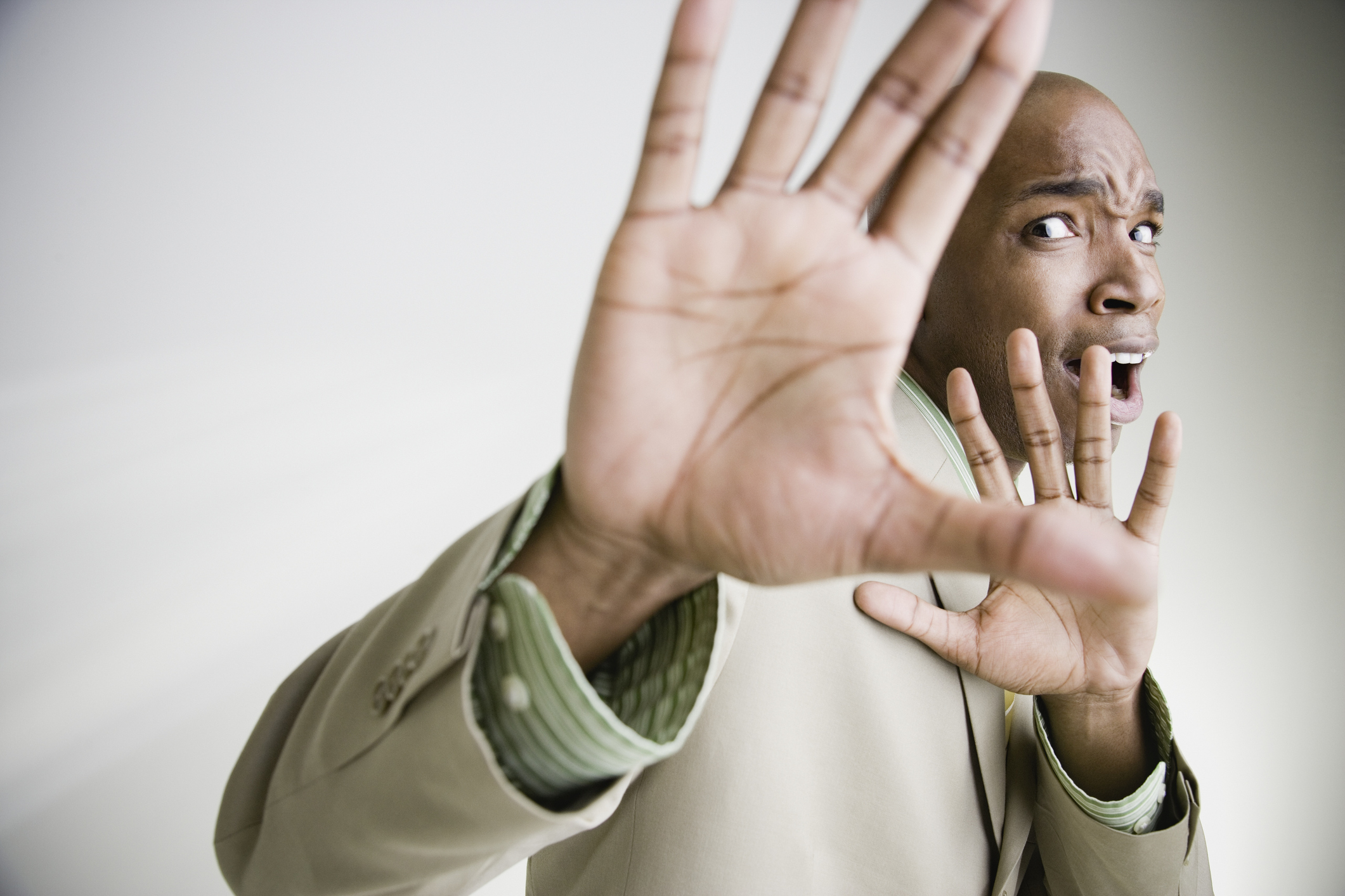 African businessman cowering with hands up