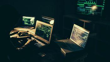 Hacker using laptop at night